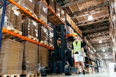 Warehouse worker doing logistics work with forklift loader