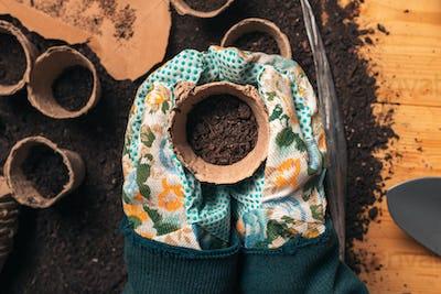 Top view of florist holding soil in flowerpot