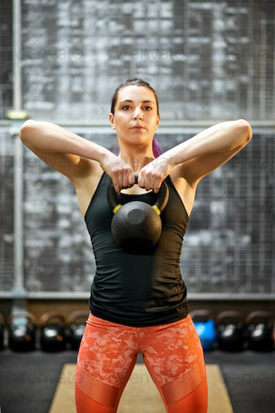 Young female athlete holding a kettlebell weight