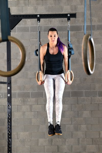 Young woman doing muscle up exercises on rings
