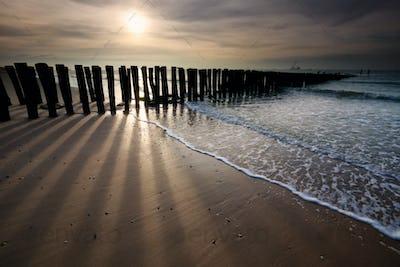 sunshine over old wooden breakwater on North sea coast
