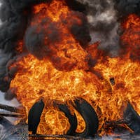 Burning Automobile Tires, Strong Flame of Red Fire, Clouds of Black Smoke in Sky