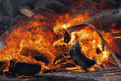 Burning Cars Tires, Strong Flame of Red Fire and Clouds of Black Fumes in Sky