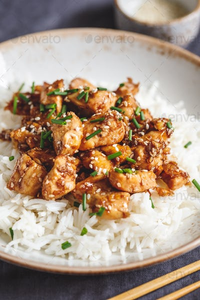 Sesame chicken pieces with white rice served spring green onions. Chinese traditional dish.