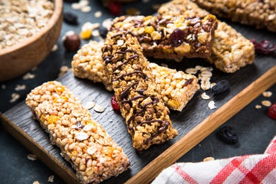 Granola bar with nuts, fruit and berries on black