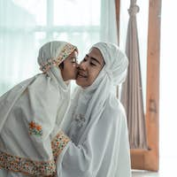 muslim young child kiss her mom after praying