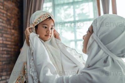 muslim mother and child with scarf to pray