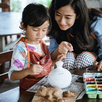 mother and daughter painting ceramic pot