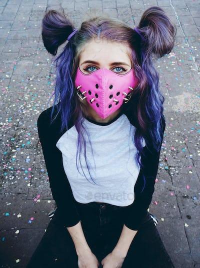 Young punk woman wearing a pink mask