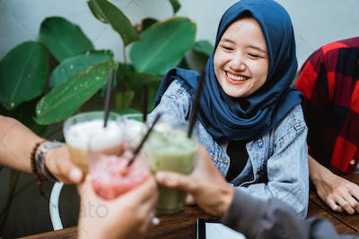 muslim woman with friend toast her drink