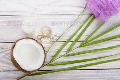 Flat lay Coconut oil in glass bottle bath sponge candle and shel