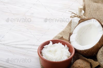 Coconut oil in brown clay bowl, glass bottle, coconut shell with