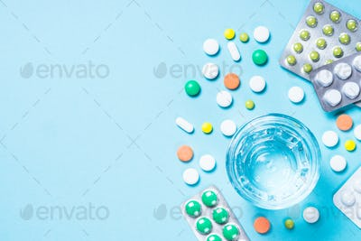 Pills and glass of water on blue top view