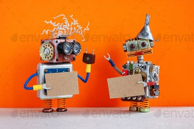 Two comical robots with a cardboards mockup.