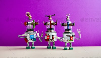 Funny glass headed ufo robots against purple wall background. Three humanoid toy robots communicate.