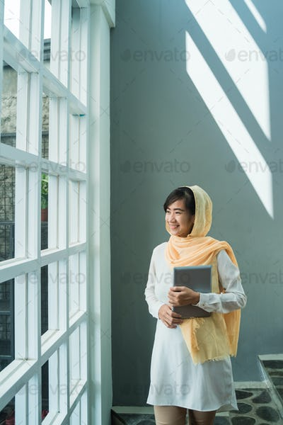 muslim woman wearing hijab using tablet pc