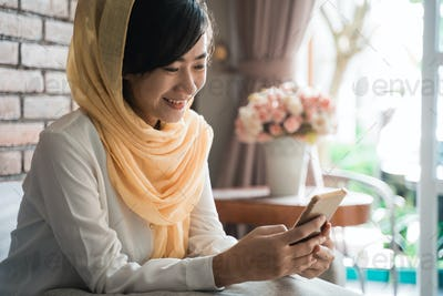 muslim woman using mobile phone at home sitting