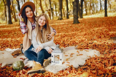 Beautiful girls have fun in a autumn park