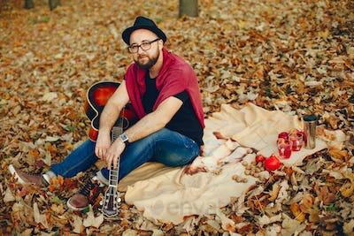 Handsome man sitting in a autumn park