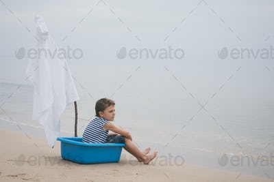 One little boy playing on the beach at the day time.