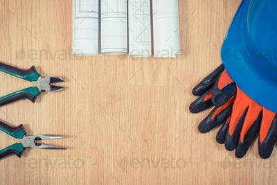 Rolls of electrical drawings, protective helmet with gloves and work tools