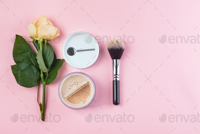 Set of cosmetics powder and brushe with rose on pink background. Makeup Accessories Top view Flat