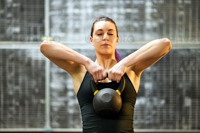 Girl working out with a kettlebell weight