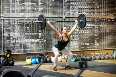 Young woman performing the snatch in a gym