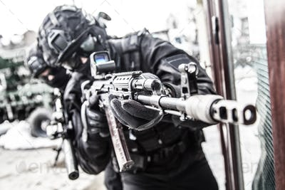 Police special reaction team member aims with gun