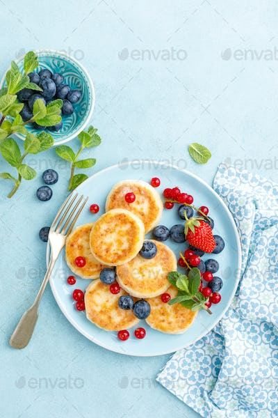 Cottage cheese pancakes, syrniki with fresh berries for breakfast