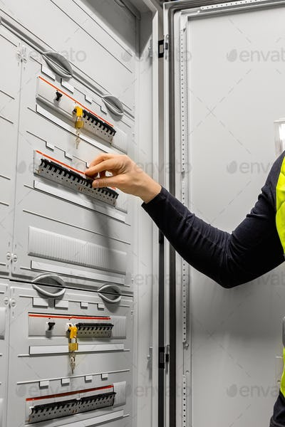 Male Electrician Checking Electric Fuse Board In Server Room