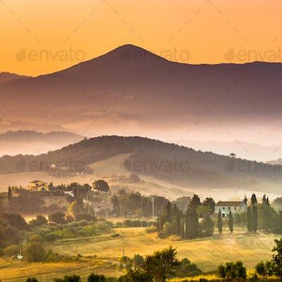 Sunrise over foggy Tuscany village