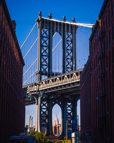 Manhattan bridge seen from a narrow alley enclosed by two brick