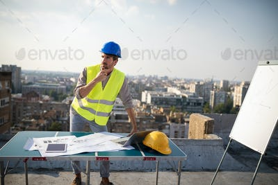 Architects, business manager and engineer meeting project at building site