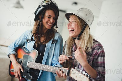 Young happy dancing girls playing guitar and partying