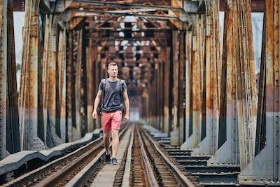 Traveler walking on railway bridge