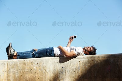 Full body cheerful man lying on wall with headphones and cellphone