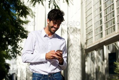 Happy handsome man standing outside in city holding cellphone