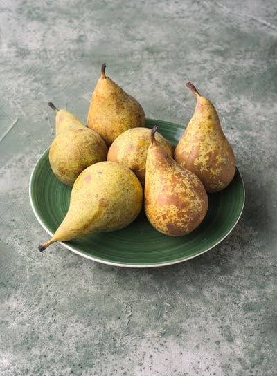 group of ripe pears in green porcelain dish on green marbling background