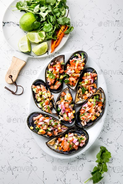 Peruvian Choros a La Chalaca. Mussels with Tomato, Onion and Cilantro Sauce. White Marble Background