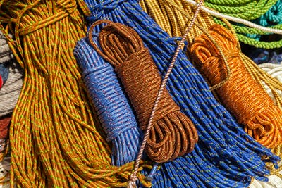 Many multicolored ropes lie on the ground