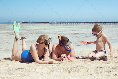 Parents and child in snorkels playing on the beach