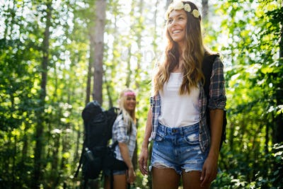 Hiker woman with backpack walking on path in summer forest
