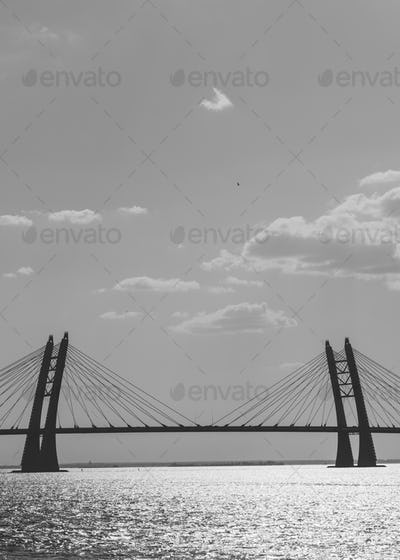 Black and white photography of modern car bridge over water.