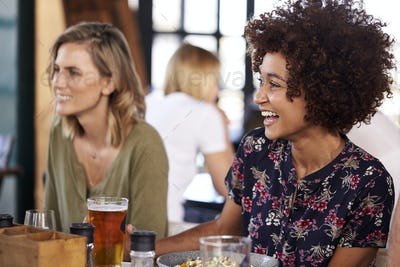 Two Young Female Friends Meeting For Drinks And Food In Restaurant
