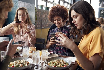 Female Friends In Restaurant Taking Picture Of Food In Restaurant To Post On Social Media