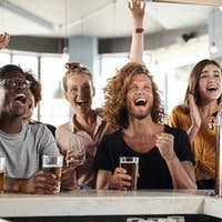 Group Of Male And Female Friends Celebrating Whilst Watching Game On Screen In Sports Bar
