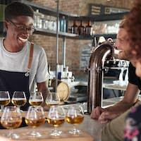 Waiter Serving Group Of Friends Beer Tasting In Bar