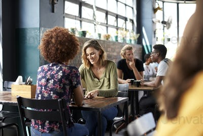 Two Female Friends Sitting At Table In Coffee Shop Talking