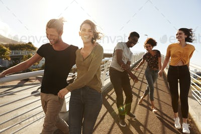 Group Of Young Friends Outdoors Walking Along Gangway Together